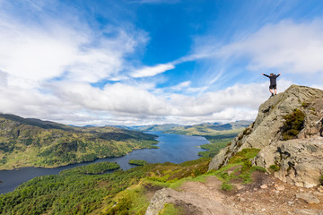 UK, Scotland, Highland, Trossachs, tourist cheering on mountain Ben A'an with view to Loch Katrine
