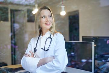 Smiling female doctor with stethoscope behind windowpane