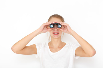 Portrait of happy  female model looking through binoculars. Searching gift concept.