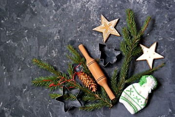 Merry Christmas and Happy New Year background: Christmas cookies stars, cuttings for cookies, fir branches and Christmas decorations. Top view, copy space.
