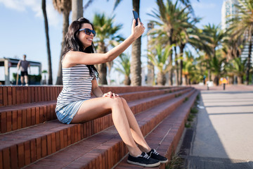 Spain, Barcelona, young woman sitting on steps at sunlight taking selfie with smartphone