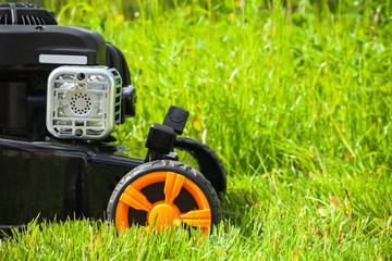 Fragment of grass mower standing on fresh green lawn