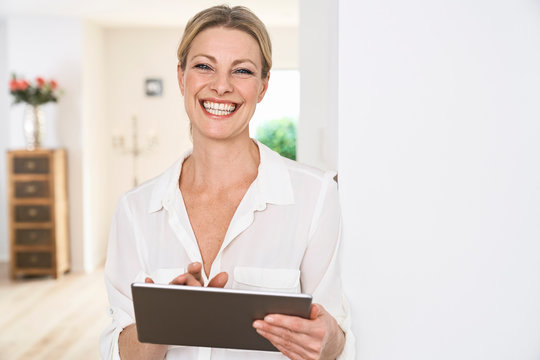 Portrait of happy woman using tablet at home