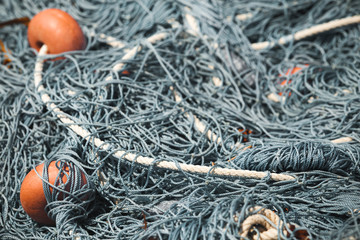 Fishing nets with red floats lay in port. Close-up