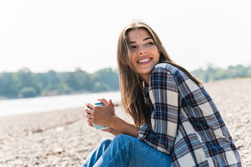 Happy young woman holding a mug sitting at the riverside