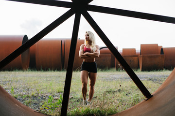 Confident athletic woman standing at industrial site