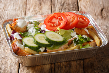 Foto op Plexiglas Assortiment Takeaway Dutch kapsalon from french fries, chicken, fresh salad, cheese and sauce in a close-up foil tray. horizontal