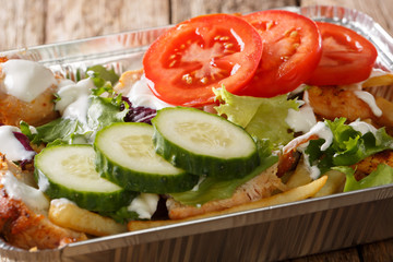 Recipe Dutch fast food kapsalon of french fries, chicken, fresh salad, cheese and sauce close-up. horizontal