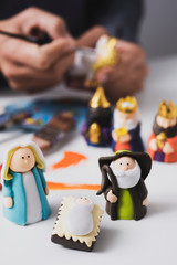 man painting figurines of a nativity scene