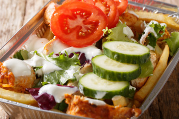 Traditional Dutch fast food kapsalon of french fries, chicken, fresh salad and sauce close-up. Horizontal