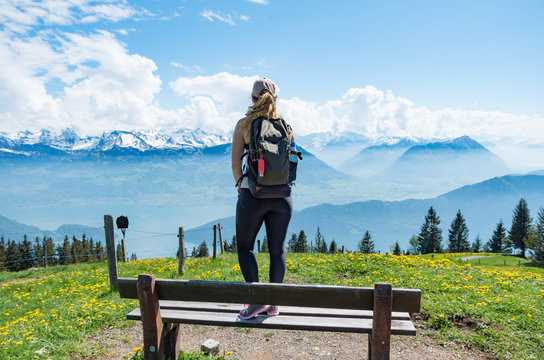 Young beautiful woman standing on a wooden bench looking out over the Swiss Alps on a sunny day