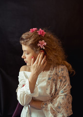 Portrait of a young romantic woman with blond curly hair in a vintage floral dress sitting over black background. Close Up of woman