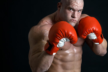 Muscular boxer in front of black background