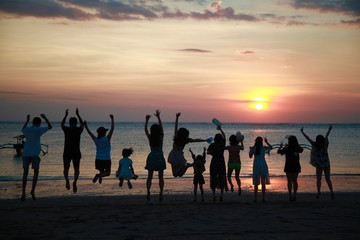 Happy people jumping on sunset background