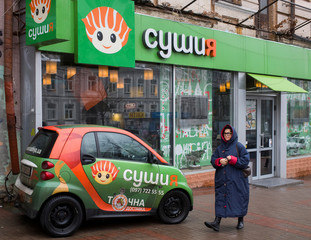 A woman walks along a street in front of a sushi restaurant in central Kiev