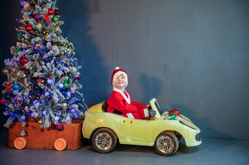 Cute boy dressed in festive costume of Santa Claus is carrying Christmas tree decorating Xmas tree with balls and garlands on a yellow car. boy plays and waits for gifts. Christmas Eve