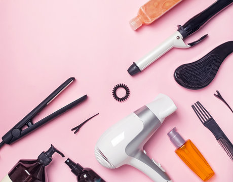 Hair styling and care items and products on pink background