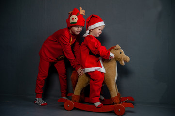 Happy children are dressed in festive costume of Santa Claus and snowman, carrying decorated Christmas tree with balls and garlands on yellow car, accompanied by rocking horse. Christmas Eve