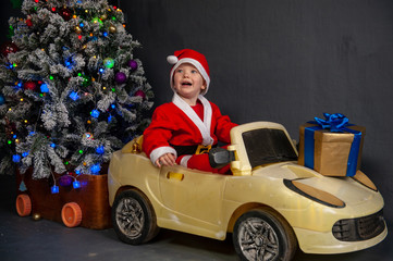 Happy child are dressed in festive costume of Santa Clausn, carrying decorated Christmas tree with balls and garlands on yellow car. Christmas Eve