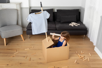 Litte girl in cardboard box playing pretend looking through paper roll