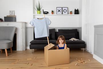 Little girl playing pretend in a cardboard box
