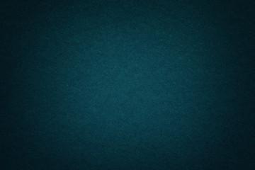 Texture of old dark blue paper background, closeup. Structure of dense deep bluish cardboard.