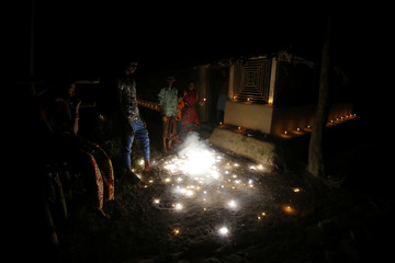 People burn firecrackers during Laxmi Puja festival on Ghoramara Island