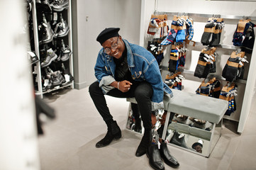 Stylish casual african american man at jeans jacket and black beret at clothes store trying new footwear.