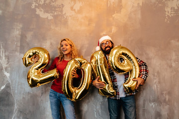 New Year. Couple. Fun. Man and woman are holding inflated numbers 2019, looking at camera and smiling, on the grey background