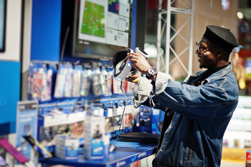 Stylish casual african american man at jeans jacket and black beret using vr glasses at electronics store.