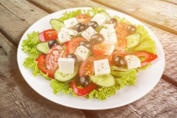 Greek salad with fresh vegetables on background