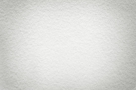 Texture of old light white paper background, closeup. Structure of dense cardboard.