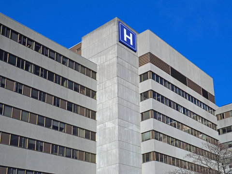 Large concrete building with  H sign for hospital