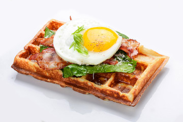 Belgian waffle on a white background. Stuffed with bacon, eggs and salad.