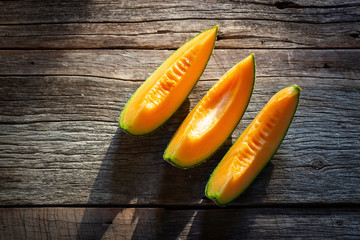 Sliced fresh sweet melon on wooden board. Orang texture and juice tast of fruit. Top view with copy space.