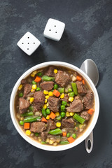 Beef stew or soup with colorful summer vegetables (pea, carrot, sweet corn, green bean, onion) in bowl, photographed overhead on slate with natural light