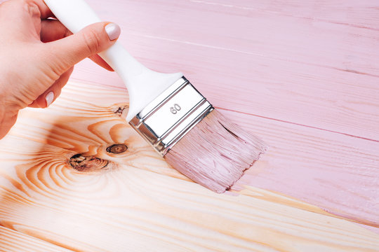 Woman's hand with white brush applying pink paint on wooden furniture. Renovation concept.