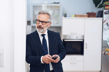 Businessman standing thinking in his house