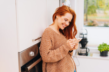 Attractive young housewife using her mobile phone
