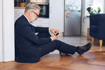 Grey-haired businessman sitting on the floor