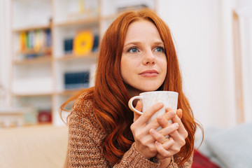 Thoughtful young woman holding a mug of coffee