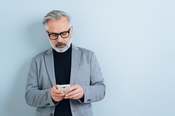 Bearded businessman texting a message on a mobile