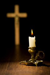 Christian religion concept, lit candle on a crucifix background