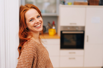 Laughing redhead woman leaning on wall at home