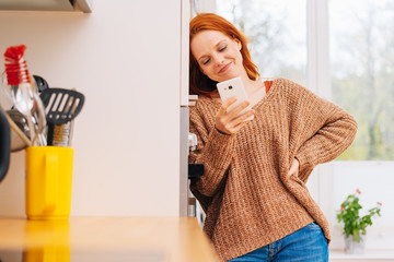 Happy, young woman using phone in home environment