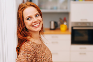 Happy, smiling, young redhead woman at home