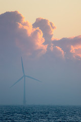 Spiritual background image with wind turbine and beautiful morning cloud. Renewable energy and sustainable development.
