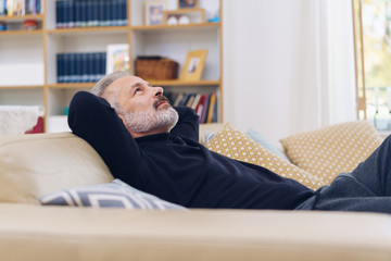 Attractive bearded man unwinding on a sofa at home