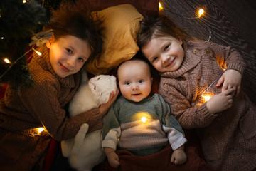 several children and cat in dark cozy interior