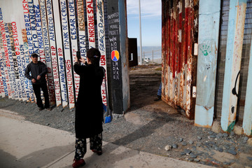 A Chinese tourist poses for pictures next to the border wall between United States and Mexico, as workers keep a door open while they repair it in Tijuana
